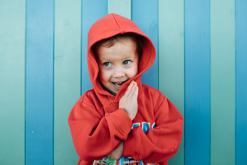 boy in red hoodie at Brighton bathing boxes, And So I Don't Forget Photography