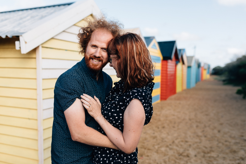 Couple hugging at bathing boxes Brighton Beach during Family Photo Session And So I Don't Forget Photography